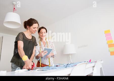 Les femmes mûres sont à 24 tissu coupe looking at digital tablet Banque D'Images