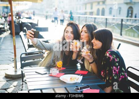 Trois jeunes femmes se faisant passer pour des selfies smartphone at waterfront cafe Banque D'Images