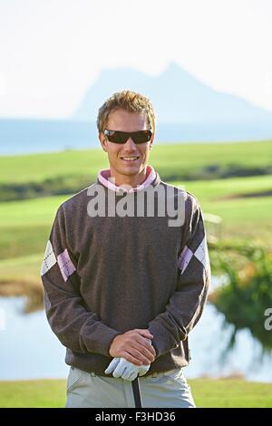 Le port de lunettes de golfeur looking at camera smiling
