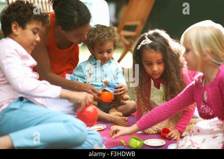 Mère et ses quatre enfants jouant à un pique-nique d'anniversaire jardin Banque D'Images