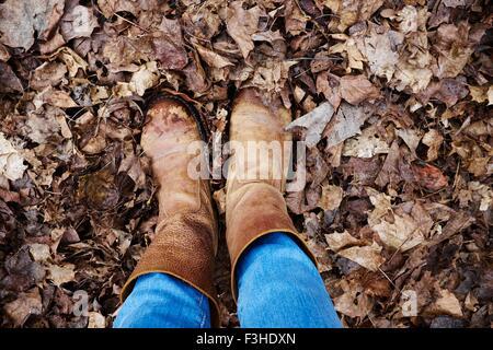 Vue aérienne de porter des bottes femme debout dans les feuilles d'automne
