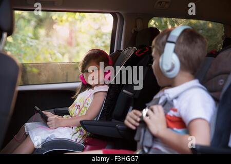 Garçon et jeune sœur portant des écouteurs et using digital tablet in location de siège arrière Banque D'Images