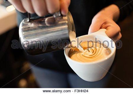 Café barista de verser le lait dans le café, mid section, close-up Banque D'Images