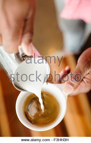 Café barista de verser le lait dans le café, Close up Banque D'Images