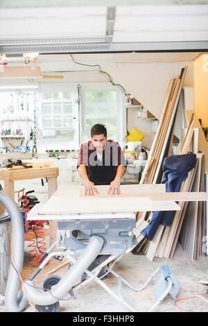 Jeune homme de porter un tablier à l'aide d'atelier scie pour couper du bois