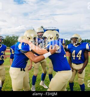 Les adolescentes et les jeunes joueurs de football américain féliciter sur terrain de football