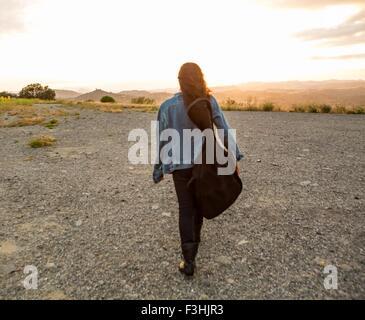 Vue arrière du jeune femme exerçant son étui à guitare au coucher du soleil Banque D'Images
