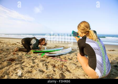 Couple on beach, young woman taking photograph of man with surfboard