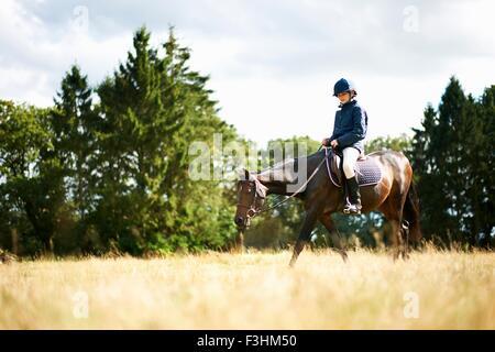 Girl l'équitation dans le champ Banque D'Images