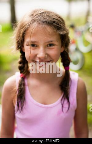 High angle portrait of young girl with pigtails smiling at camera Banque D'Images