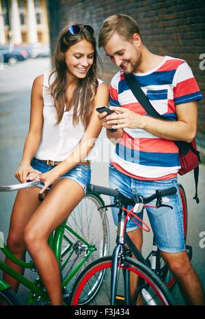 Jeune couple à bicyclette à l'aide de l'extérieur du téléphone cellulaire Banque D'Images
