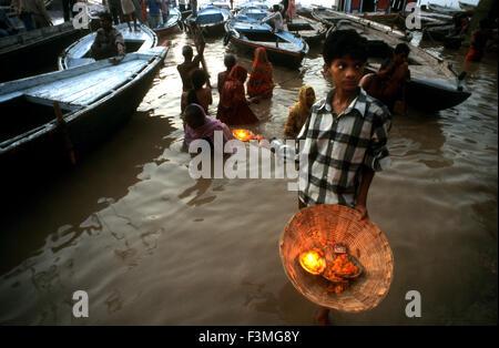Garçon vente de fleurs et Deepak (lampe à huile et fleurs flottantes) à Varanasi, Inde. Varanasi, Uttar Pradesh, Banque D'Images