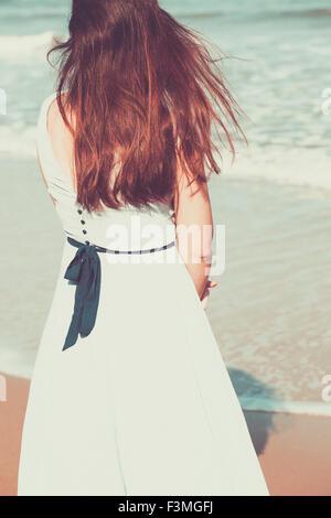 Jeune femme historique sur la plage portant une robe bleue Banque D'Images
