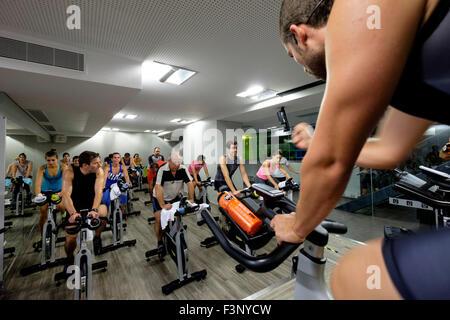 Instructeur de conditionnement physique encourage les gens à cheval des bicyclettes stationnaires pendant un cours Banque D'Images
