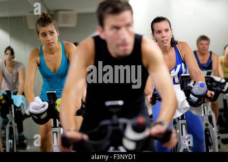 Les jeunes femmes équitation vélo stationnaire pendant un cours de gym spinning Banque D'Images