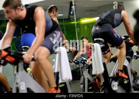 Jeune femme équitation vélo stationnaire pendant un cours de gym spinning Banque D'Images