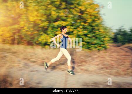 Jeune femme tournant sur un chemin rural au coucher du soleil dans la forêt d'automne. Fond sports Lifestyle