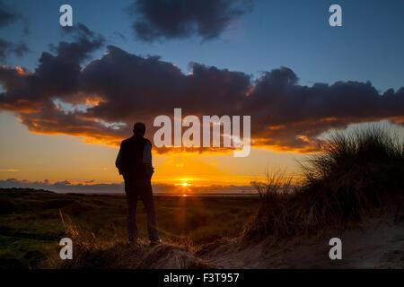 Southport, Merseyside, UK 12 Octobre, 2015. L'homme Silhouette. Météo britannique. De soleil colorés sur la mer Banque D'Images