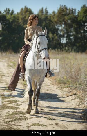 Belle fille à cheval sur le cheval blanc dans un champ Banque D'Images