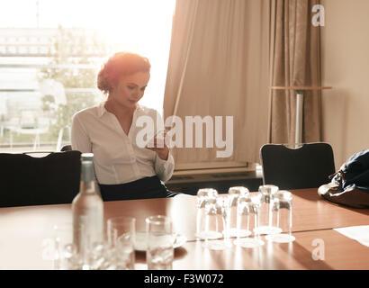 Portrait of young businesswoman sitting in business salle de conférence à l'aide de téléphone mobile. Female executive Banque D'Images