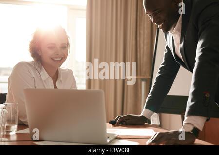 Portrait of happy young business équipe travaillant ensemble sur ordinateur portable. Businessman and businesswoman séance dans la salle de conférence.