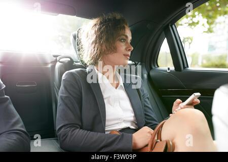 Young businesswoman pour se rendre au travail et dans la voiture de luxe sur le siège arrière holding mobile phone Banque D'Images