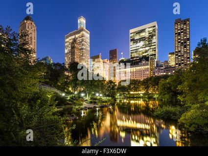 Grattes-ciel de Manhattan illuminée en début de soirée la lumière. Les bâtiments reflètent dans l'étang du parc Banque D'Images