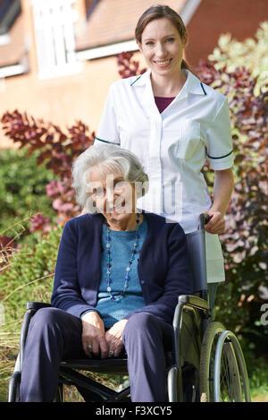 Portrait of Senior Woman soignant poussant en fauteuil roulant Banque D'Images
