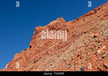 Les roches rouges et orange d'une haute falaise, offrent un contraste saisissant avec le bleu ciel dans le désert Banque D'Images