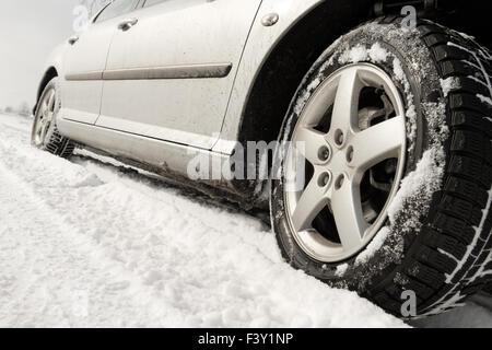 Close up d'un des pneus de voitures sur une route enneigée Banque D'Images