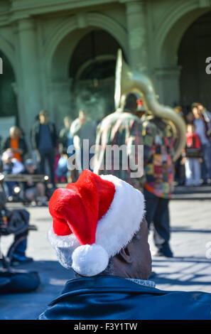 Vue arrière de man wearing Santa hat de divertissement par des musiciens de rue, Jackson Square, Quartier Français, Banque D'Images