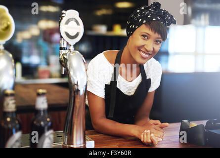 Young African American small business owner vêtue d'un foulard et d'un tablier s'appuyant sur le comptoir de sa Banque D'Images