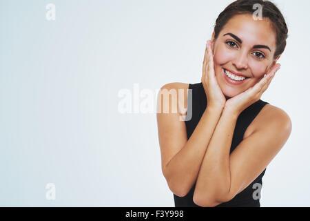 Belle femme avec une belle peau, smiling at camera holding ses joues. Copier l'espace. Portrait isolé Banque D'Images