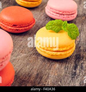 Certains macarons appétissants avec différentes couleurs et saveurs sur une table en bois rustique Banque D'Images