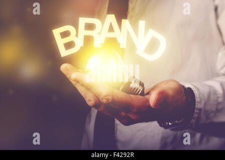 Idée de marque concept avec businessman holding ampoule, tons rétro droit, selective focus.