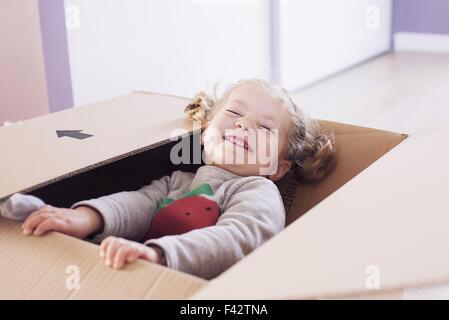 Petite fille jouant en boîte carton, portrait Banque D'Images
