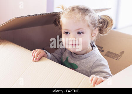 Little girl playing in cardboard box Banque D'Images