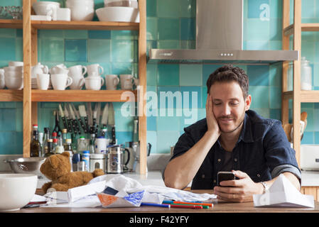 L'homme à la maison using smartphone Banque D'Images