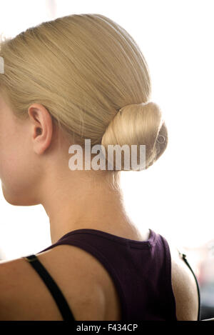 Femme avec cheveux disposés en un chignon Banque D'Images