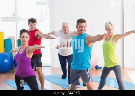 Les gens qui font de la classe guerrier poser dans le yoga Banque D'Images