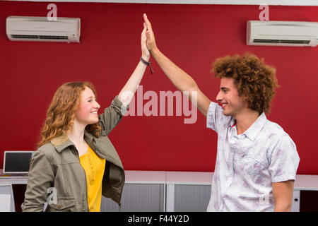 Businessman and woman high fiving Banque D'Images