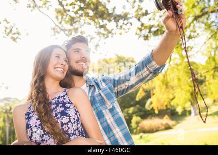 Cute couple avec retro selfies caméra dans le parc Banque D'Images