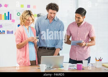 Les jeunes gens d'affaires à la recherche à un ordinateur portable Banque D'Images