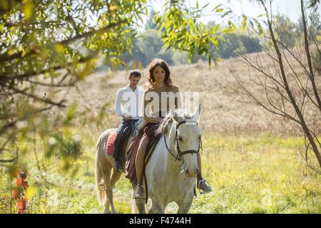 Jeune couple amoureux riding a horse Banque D'Images