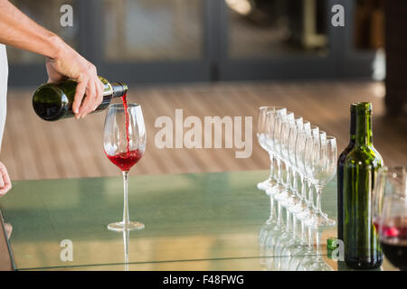 Man pouring red wine in a glass Banque D'Images