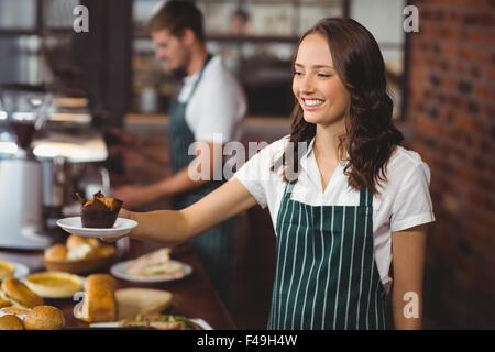 Smiling waitress serving un muffin Banque D'Images