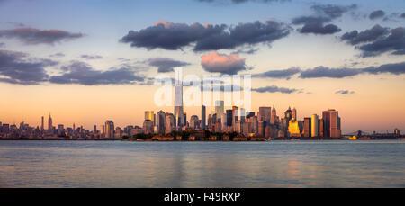 Gratte-ciel de Manhattan, le quartier financier et Ellis Island Panorama au coucher du soleil, New York City, USA