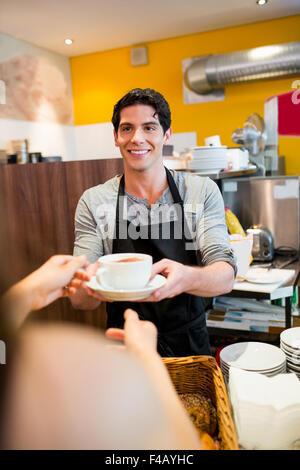 Waiter serving cappuccino pour client Banque D'Images