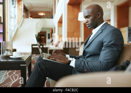 Image d'occupé young businessman working on laptop. African businessman sitting in hotel lobby l'attente de quelqu'un. Banque D'Images