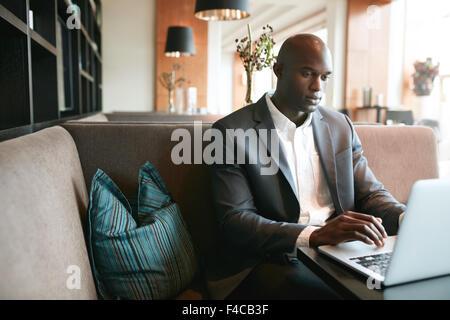 Image de jeune homme assis au café travaillant sur ordinateur portable. African businessman at coffee shop surf Banque D'Images
